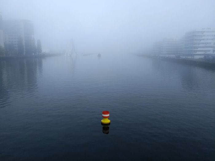 Building River Travel Destinations Overcast Mood Atmospheric Mood Yellow Red Buoy Contrast Abstract Leadership Concept Center Waterfront Sky Reflection Atmospheric Mood Reflections In The Water Water Fog Cold Temperature Weather Sky Buoy Foggy Floating Floating On Water Float Mist