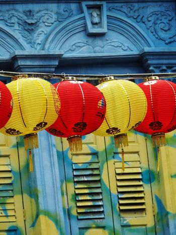 Red and yellow lanterns in front of blue shophouse in Chinatown Singapore Multi Colored Hanging Red Lantern No People Low Angle View Day Indoors  Close-up EyeEmNewHere Architecture Building Exterior Yellow Color Shophouse Lanterns Shophouse Singapore Chinatown Singapore Chinatown