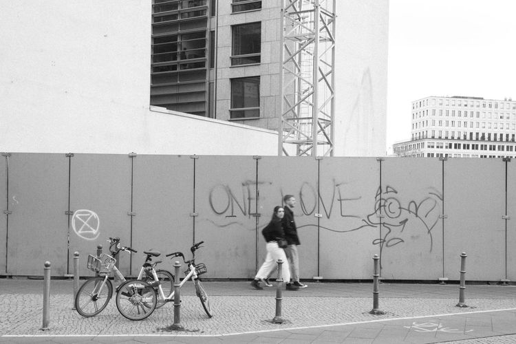 . Building Exterior Architecture Built Structure Full Length Real People City Transportation Bicycle One Person Lifestyles Day Women Men Leisure Activity Wall - Building Feature Building Art And Craft Land Vehicle Outdoors Berlin OneLove Tagsforlikes Graffiti Potsdamer Platz Blackandwhite Strideby Couple The Street Photographer - 2019 EyeEm Awards