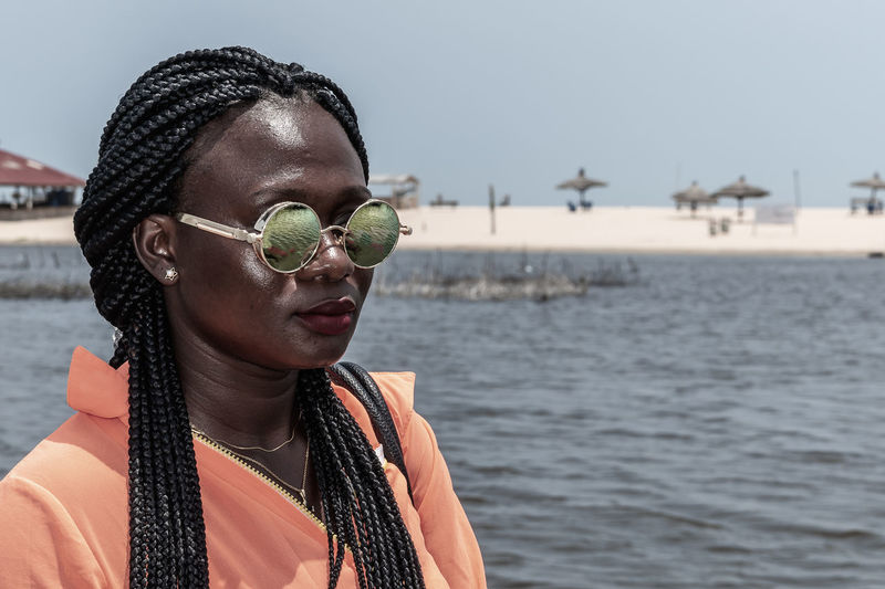 Africa woman with sunglasses from ghana enjoying the sun on a beach in accra.