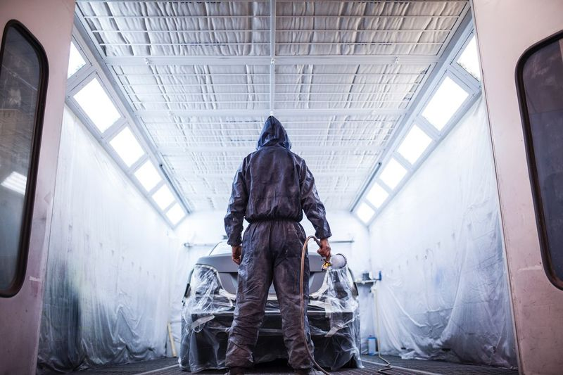 painter posing in front of the booth before painting a car Painting Workshop Dirty Lights Uniform Plastic Job Work Back Man Air Repair Cabin Car Painter Automobile Indoors  Rear View Men One Person Low Angle View Warm Clothing