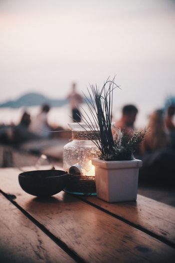 Glass Jar By Potted Plant And Bowl On Table At Beach During Sunset