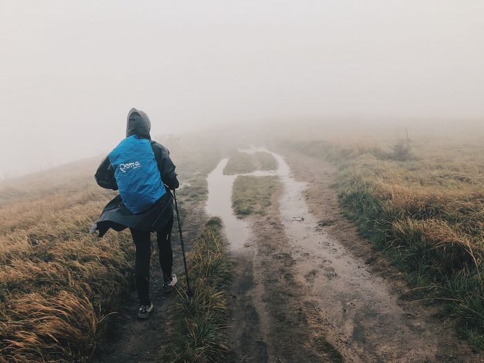 Rear view of man on landscape during foggy weather