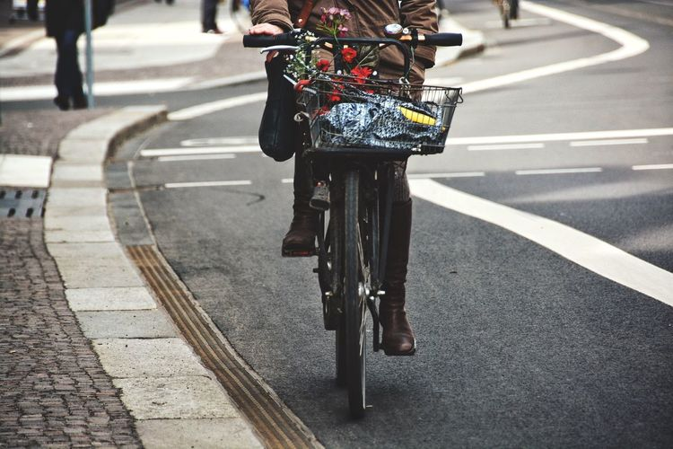 Low section of woman bicycling on road