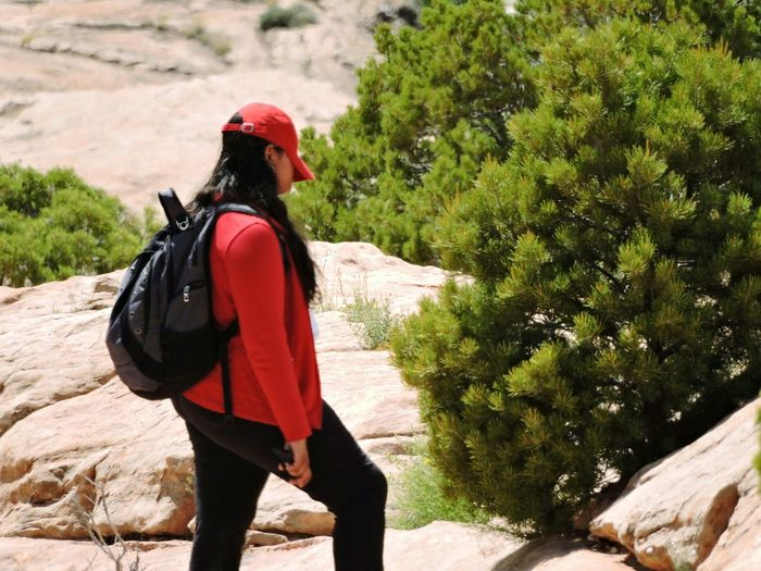One Person Young Adult One Woman Only Outdoors Hiking Backpacking Desert Landscape American Southwest Arid Landscape Non Recognizable Female Brunette Female Hiker Rocks Sun Full Sun Shading Face Hat Red Color Sun Protection Spf Harsh Sun Summer Arches National Park Utah