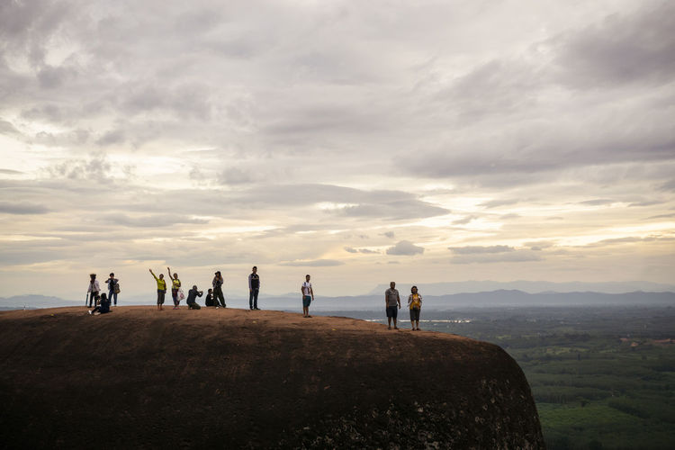 People standing on rock against sky