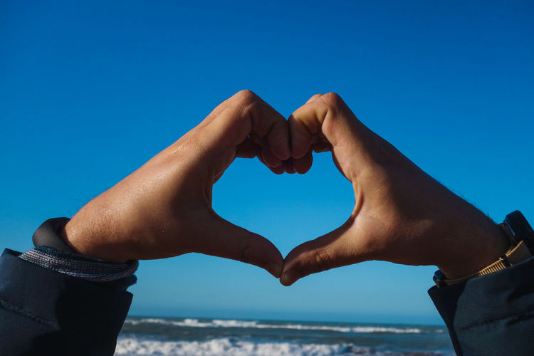 Cropped hands making heart shape at beach against clear blue sky