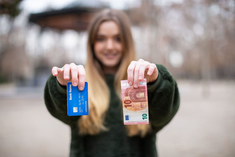 Young lady demonstrating plastic card and cash to camera while standing in park Woman Credit Card Banknote Choice Showing Young Park Currency Cash Pay Finance Money Investment Transaction Plastic Female Alternative Consumerism Demonstration Modern Contemporary Option Lady Decision Economy Wealth Savings Bill Electronic Euro Europe Offering Offer Budget Blurred Background Horizontal Outdoors Copy Space Portrait One Person