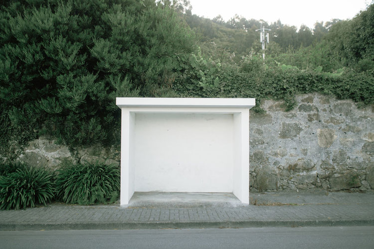 Built structure by trees against wall