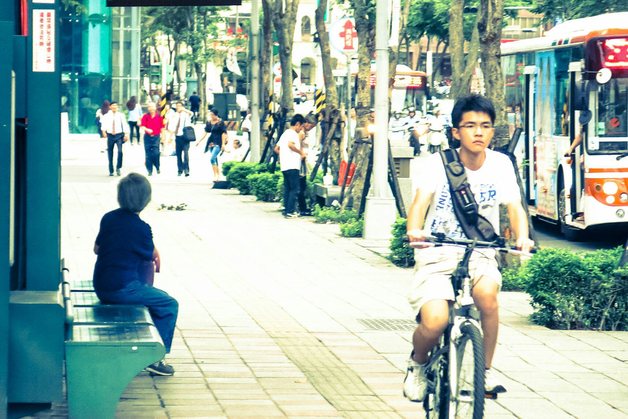 bicycle, real people, transportation, riding, mode of transport, street, land vehicle, outdoors, cycling, rear view, full length, casual clothing, city, city life, day, lifestyles, leisure activity, motion, road, architecture, one person, young adult, people