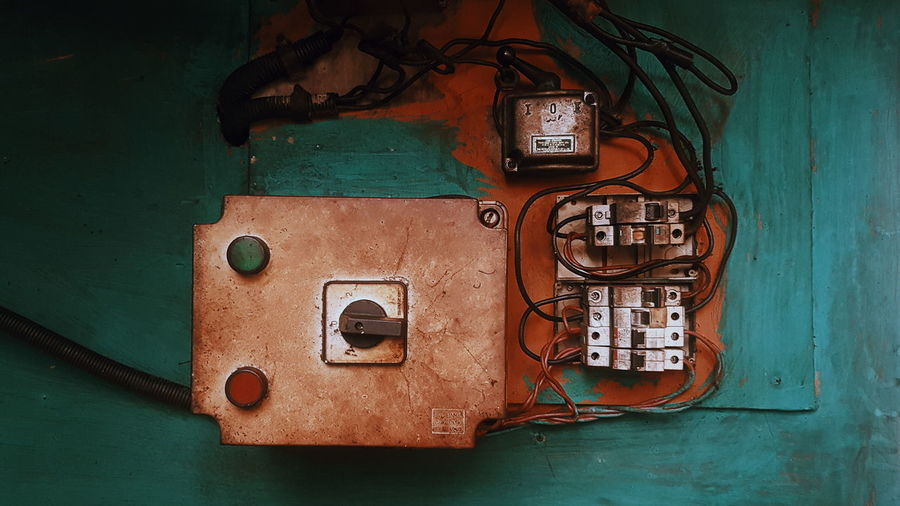 Close-up of damaged electric fuse box on wall