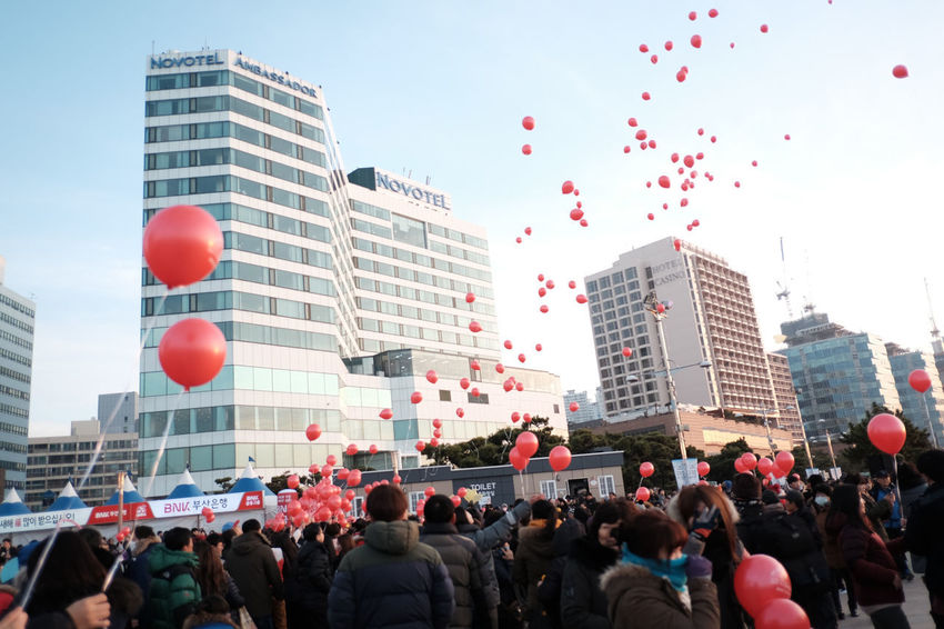 Architecture Balloon Building Exterior Built Structure Celebration City Crowd Day Large Group Of People Men Modern Outdoors People Real People Red Sky Skyscraper Women