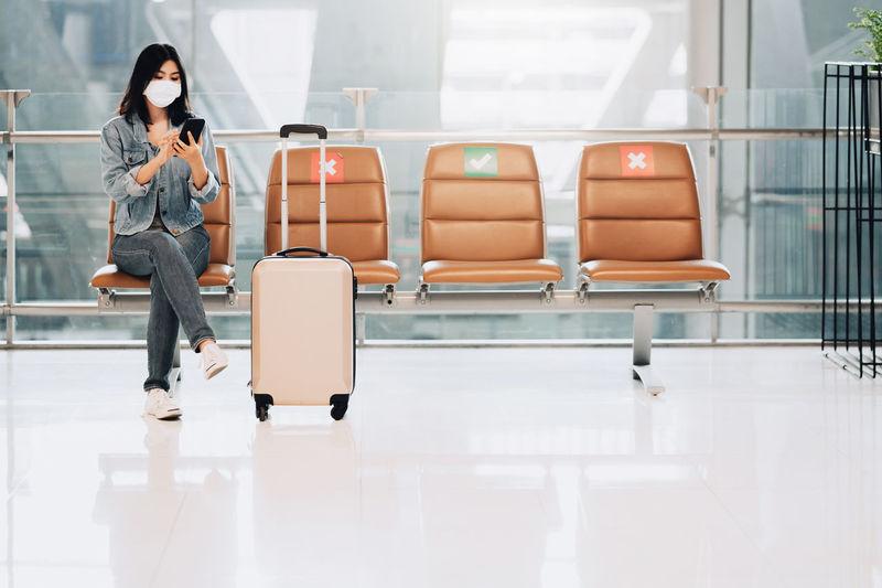 Full length of man using mobile phone in airport