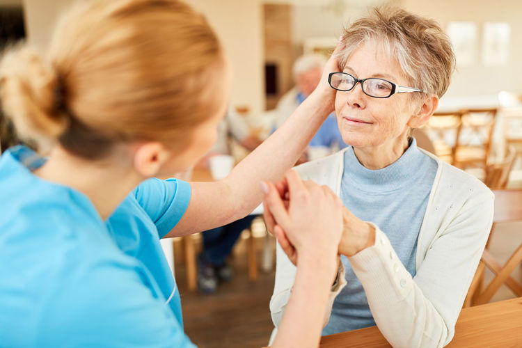 Nurse consoling senior woman at rehab center
