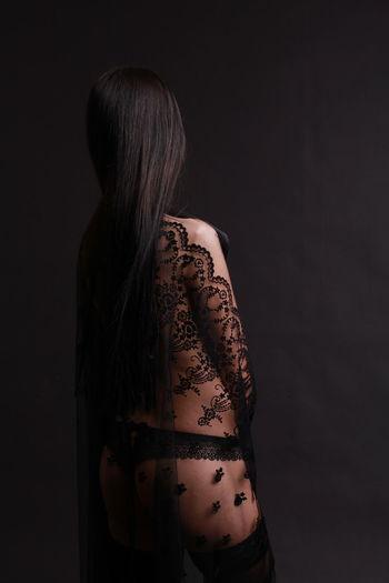 Seductive Woman Standing Against Black Background