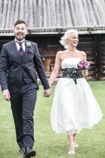 Portrait Of Smiling Groom With Bride Walking In Yard
