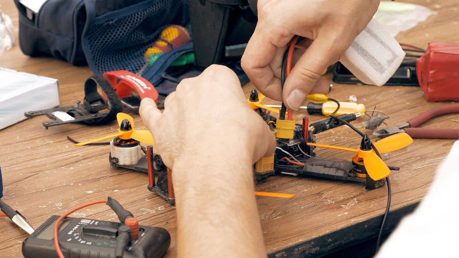 Cropped hands of man repairing quadcopter at workshop