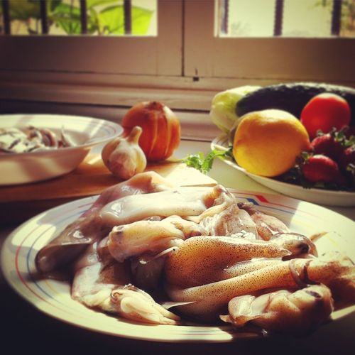 Close-up of squid in plate with fruits on table