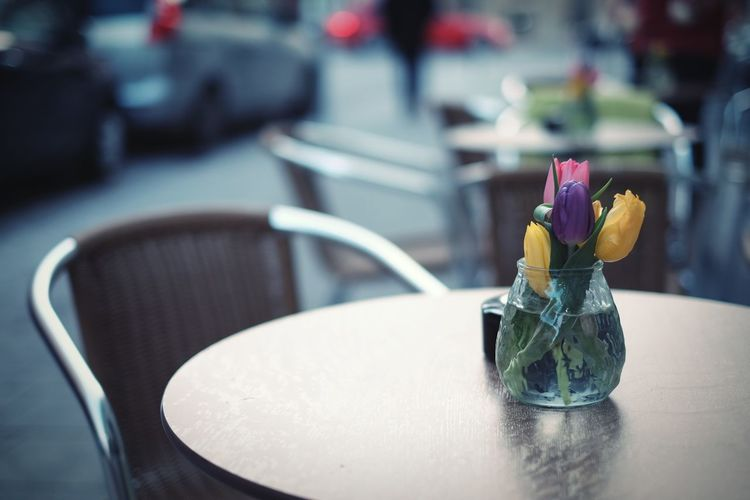 Colorful tulip flowers in vase on table at sidewalk cafe