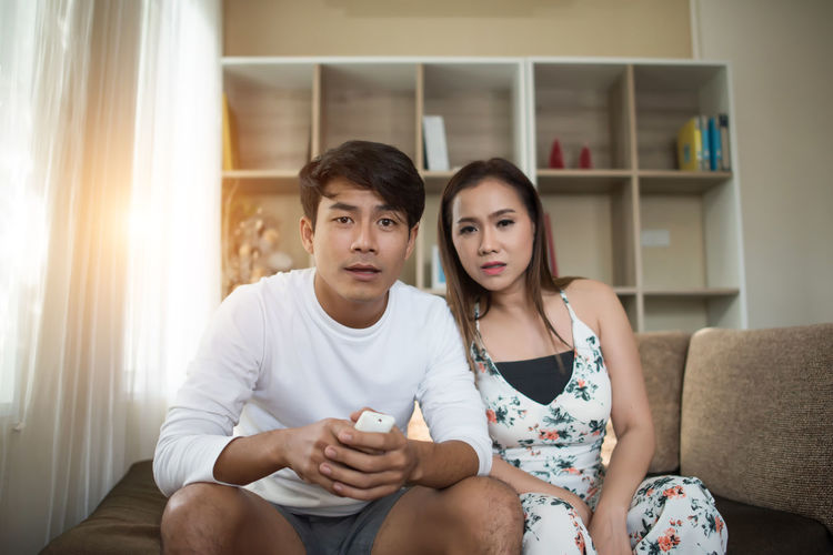 Two People Sitting Togetherness Front View Furniture Lifestyles Young Adult Sofa Indoors  Young Women Domestic Life Home Interior Three Quarter Length Domestic Room Couple - Relationship Bonding Women Casual Clothing Young Men Holding Living Room
