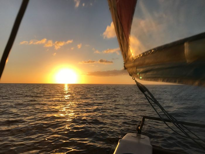 Sailboat sailing in sea against sky during sunset