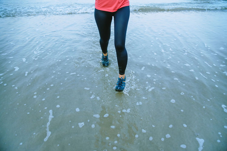 Low section of woman running at beach