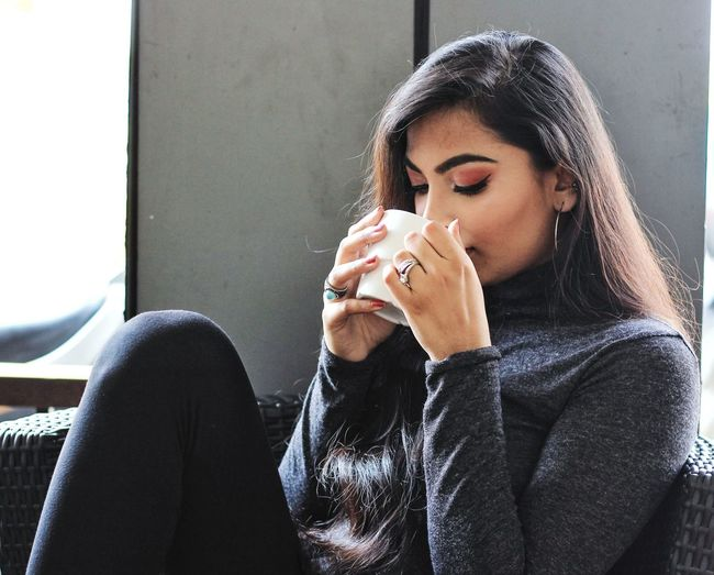 Young Woman Drinking Coffee While Sitting On Sofa