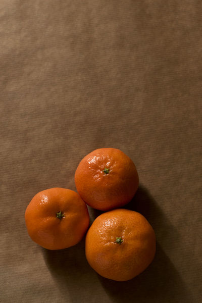 Three clementines on brown paper with dramatic lighting Citrus  Freshness Brown Brown Paper Citrus Fruit Clementine Clementines Food Fruit Healthy Healthy Eating Healthy Food Ingredient Light And Shadow Mandarins Minimal Minimalism Monochromatic Monochrome Mood Obst Orange Color Peel Pile Still Life Three