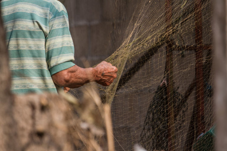 Midsection of farmer holding net