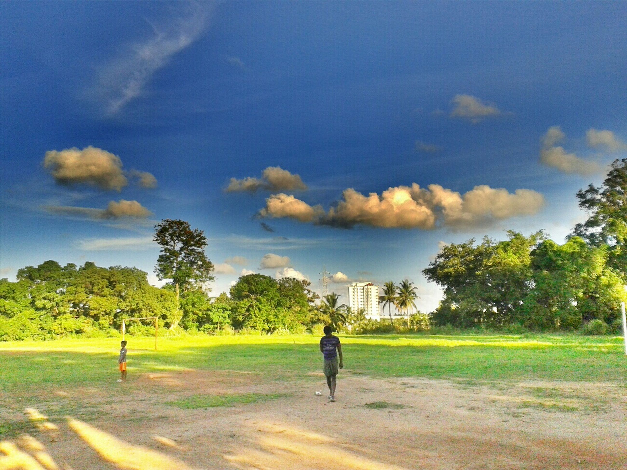 full length, lifestyles, sky, tree, leisure activity, walking, rear view, men, bicycle, road, cloud - sky, transportation, grass, casual clothing, shadow, sunlight, cloud, riding