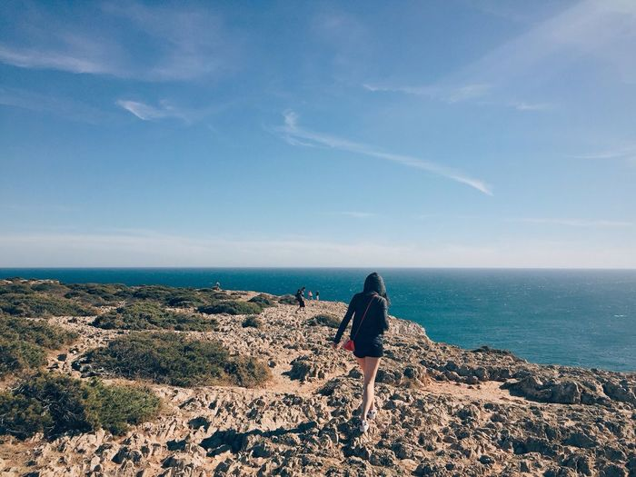 Rear view of woman walking rock formation by sea against sky