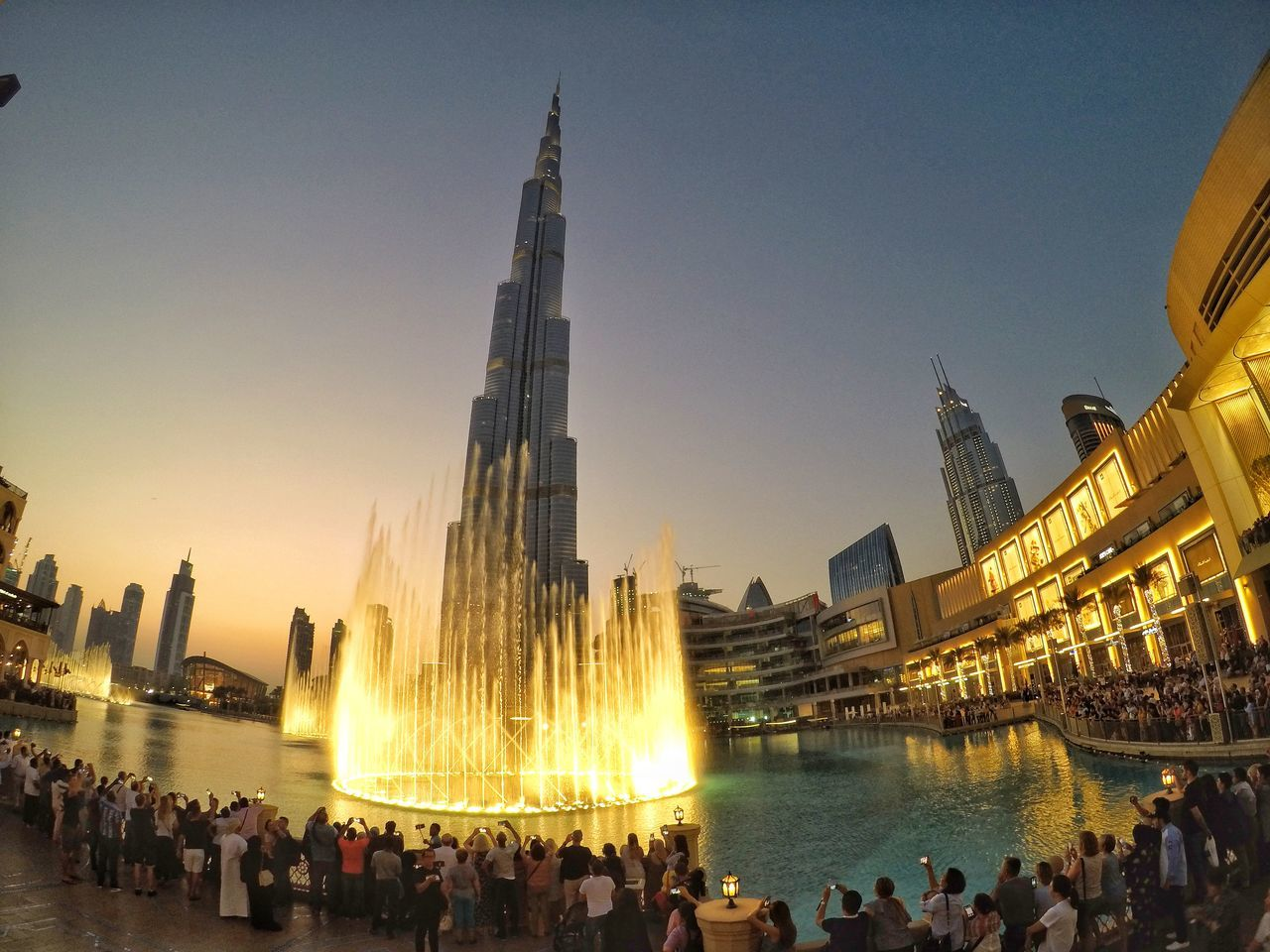 large group of people, real people, built structure, building exterior, architecture, spirituality, tourism, men, women, water, lifestyles, religion, leisure activity, place of worship, travel destinations, illuminated, travel, sky, outdoors, clear sky, crowd, togetherness, city, day, adult, people