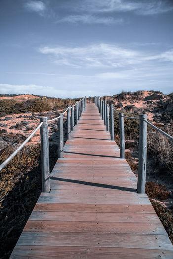 View of wooden bridge over water against sky