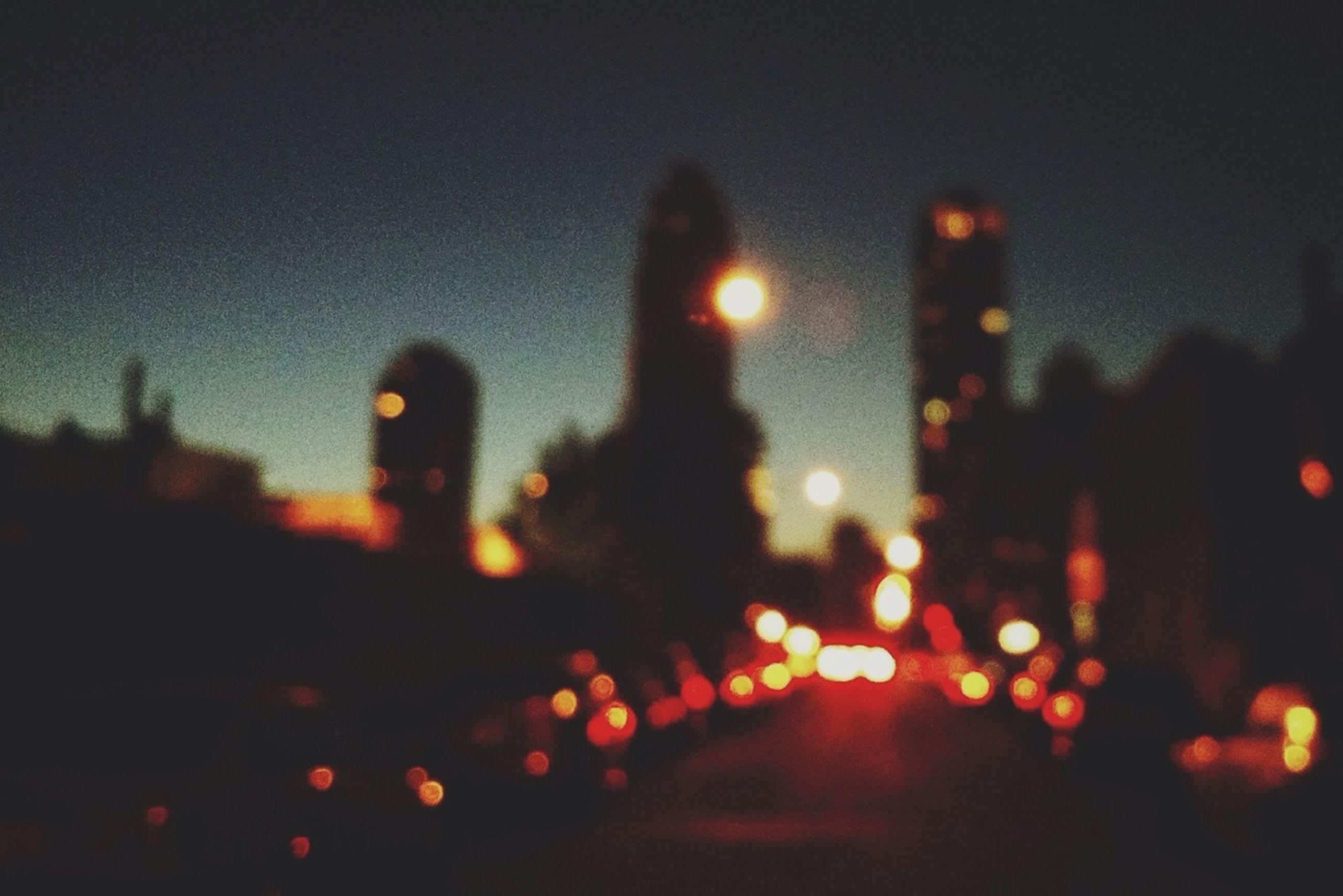 illuminated, night, city, building exterior, defocused, architecture, built structure, street, street light, lighting equipment, light - natural phenomenon, lens flare, road, dark, city life, sky, glowing, cityscape, outdoors, light