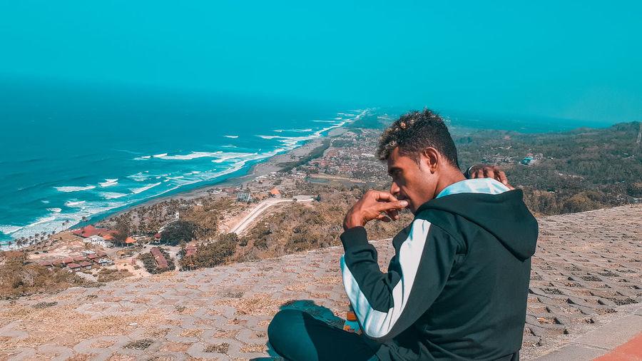 Full length of man sitting on rock at sea shore