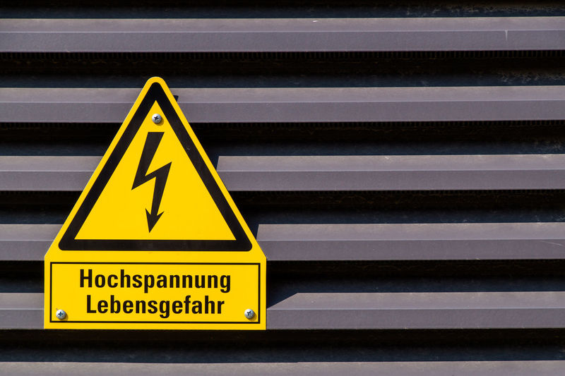 Close-up of high voltage sign on metallic wall