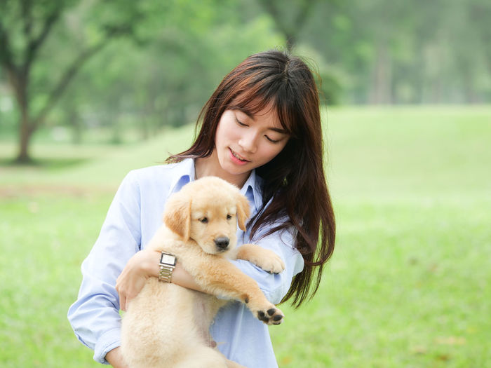 Adult Canine Dog Domestic Domestic Animals Emotion Focus On Foreground Grass Hair Hairstyle Love Mammal One Animal One Person Pets Positive Emotion Real People Smiling Teenager Women Young Adult