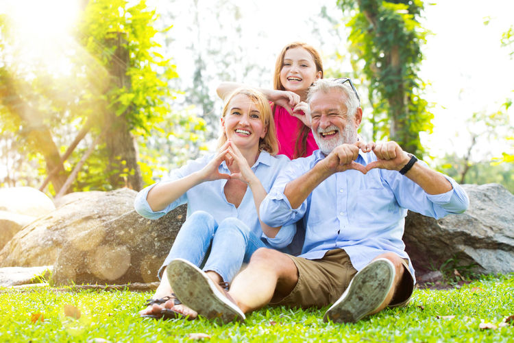Portrait of smiling family making heart shape while sitting in park