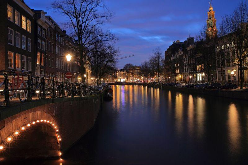 Canal amidst illuminated buildings against sky at dusk