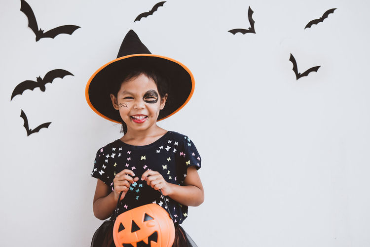 Portrait of cute playful girl with spooky make-up at home during halloween