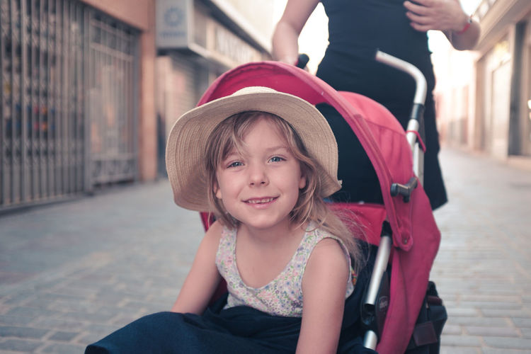Portrait Of Cute Girl Sitting In Baby Carriage