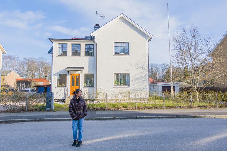 Full length of woman walking on road against buildings
