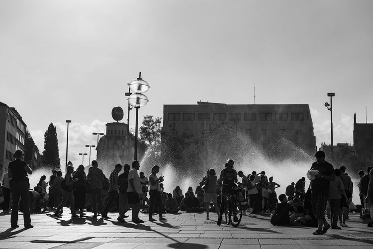 Low angle view of people by water fountain in city