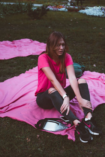 Millenial Pink Parks And Recreation Day Full Length Grass Leisure Activity Lifestyles Mobile Phone Nature One Person Outdoors People Pink Color Portable Information Device Real People Sitting Technology Wireless Technology Young Adult Young Women