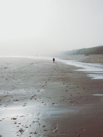 Distance view of person walking at beach against sky