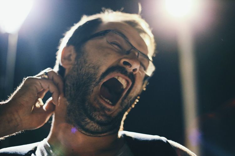 Man yawning One Man Only One Person Lens Flare Mid Adult Headshot People Beard Young Adult Close-up Human Body Part NotYourCliche Soft Focus Bokeh Bokeh Photography Yawning Yawn Man Yawning This Is Masculinity Stories From The City