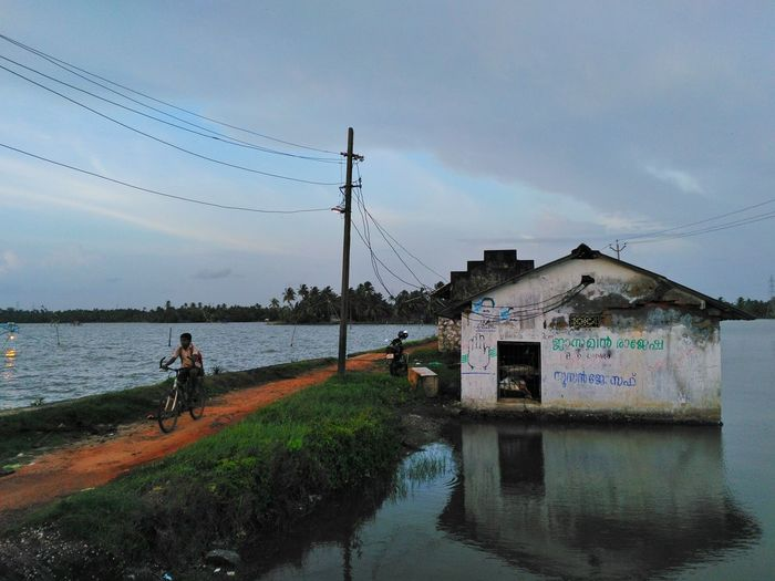An evening view from kumbalangi. A backwater village. Water Sky Building Exterior Architecture Cloud - Sky Built Structure Power Line  Day Footpath Tranquil Scene Cloud Outdoors Calm Nature Solitude Scenics Waterfront Riverbank Evening Kerala People And Places Boy Bicycle