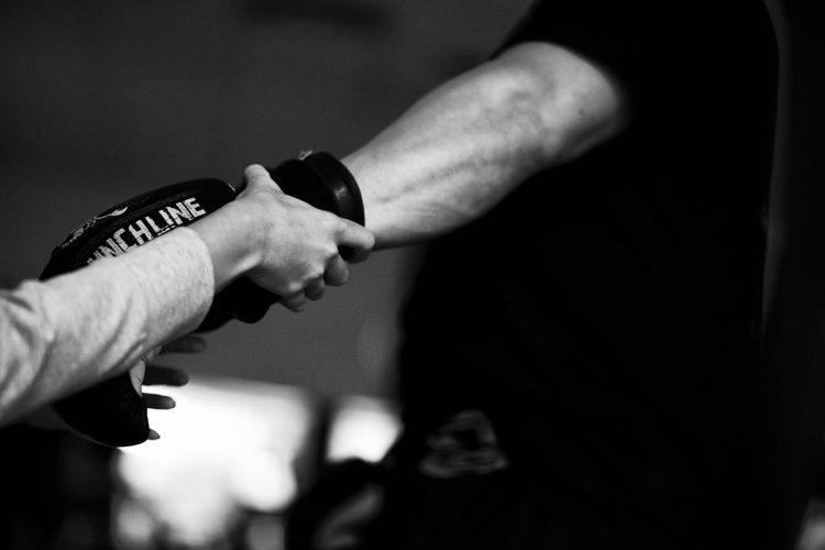 Close-up of referee examining gloves of boxer