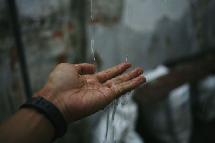 Close-up of wet hand in rainy season
