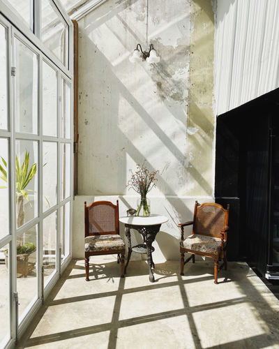 Empty chairs and table against window at home